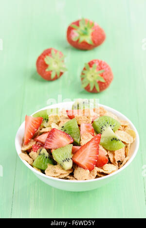 Cornflakes with strawberry and kiwi slices in white bowl on green table - Stock Photo