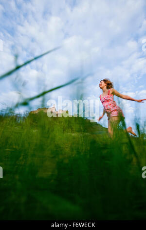Young woman running over a meadow, Riegersburg castle in background, Styria, Austria
