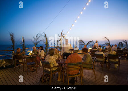 Passengers enjoying drinks on the deck of cruise ship MS Delphin  Passat Kreuzfahrten  at dusk, Caribbean Sea - Stock Photo