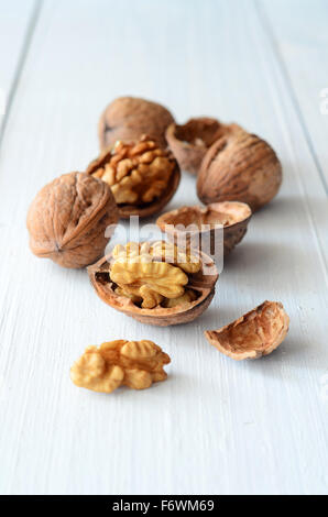 Walnut kernels and whole walnuts on rustic old wooden table - Stock Photo