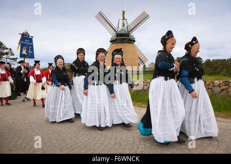 Women in traditional frisian costumes, in front of a windmill, Nebel, Amrum island, North Sea, North Friesland, - Stock Photo