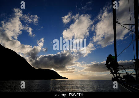 Man on a bow of a sailing boat, Cape Froward in background, Strait of Magellan, Chile - Stock Photo