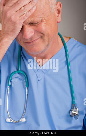 Distraught doctor wearing blue scrubs, with his hand on his head/face. - Stock Photo