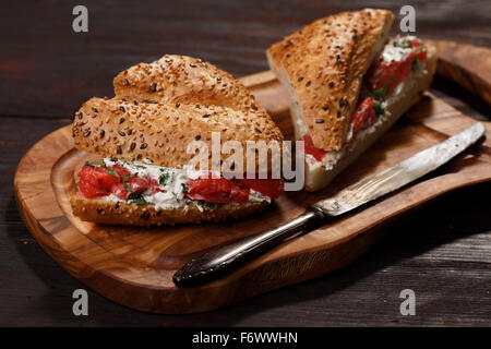 Sandwich from wholegrain bread with salmon, mild creamy cheese and herbs - Stock Photo