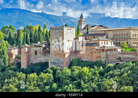 GRANADA ANDALUCIA SPAIN THE ALHAMBRA WITH STORM CLOUDS OVER THE SIERRA NEVADA AND AUTUMNAL TREES - Stock Photo