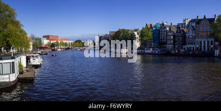 Panoramic view on Amstel river, Canal houses and Houseboats from Bridge in Amsterdam (North Holland, The Netherlands - Stock Photo
