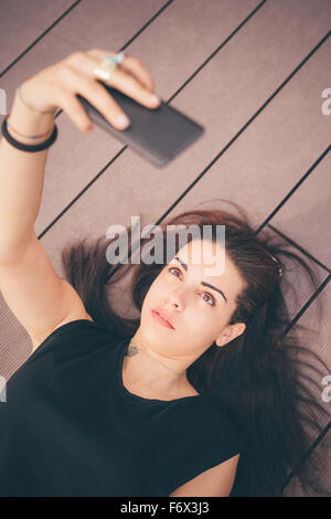 Young beautiful reddish brown hair caucasian girl lying on a sidewalk using a smartphone taking selfie - technology, - Stock Photo