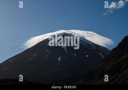 A cap of cloud illuminated by the rising sun on top of Mount Ngauruhoe, Tongariro crossing; New Zealand - Stock Photo