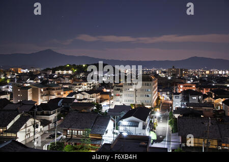 Streets and buildings illuminated at dusk, with silhouetted mountains in the distance; Kyoto, Japan - Stock Photo