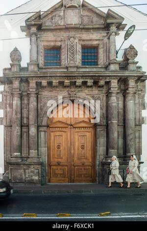Two nuns walking in front of the Colegio Sagrados Corazones in Quito, Ecuador. - Stock Photo
