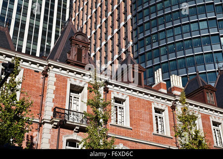 Residential building and trees with skyscrapers behind; Tokyo, Japan - Stock Photo