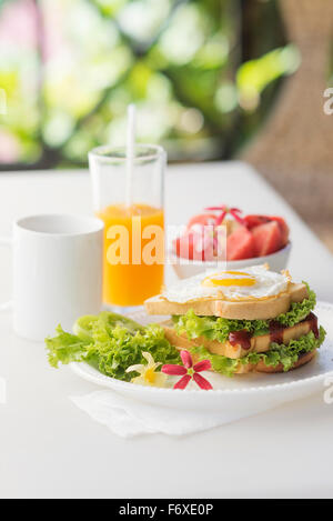 healthy breakfast set with egg sandwich and fruit salad plus coffee and orange juice - Stock Photo
