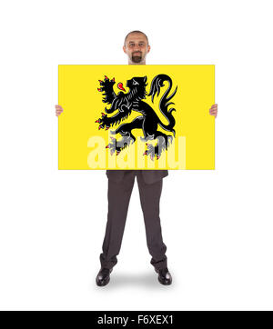 Smiling businessman holding a big card, flag of Flander, isolated on white - Stock Photo