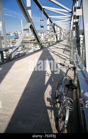Folding Bike parked over pedestrian truss bridge leads above the marina Port forum in Barcelona - Stock Photo