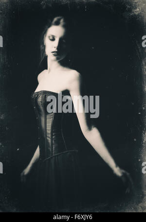 Dramatic retro portrait of a beautiful sad gothic girl among the dark. Old film effect, black and white - Stock Photo