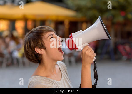Angry young woman yelling into a megaphone as she stands on an urban street venting her frustrations during an open - Stock Photo