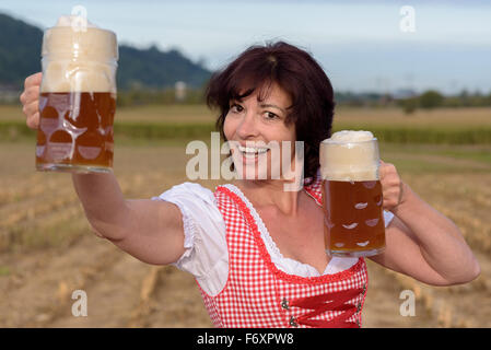 Happy attractive young Bavarian woman celebrating the Oktoberfest raising two large glass tankards filled with cold - Stock Photo