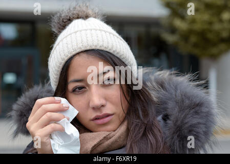 Sad tearful woman in warm winter fashion holding a handkerchief to her face to dry the tears from her eyes looking - Stock Photo