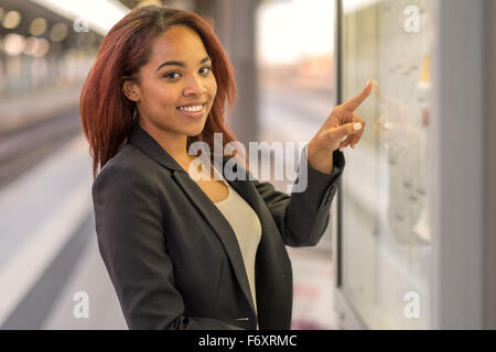 Attractive young African American woman consulting a train timetable finding her entry with her finger as she smiles - Stock Photo