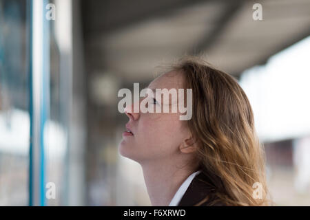 Young woman checking a timetable or notice board reading the information with a serious expression of concentration, - Stock Photo