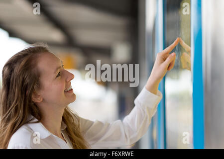 Young woman reading a train timetable on an open-air platform as she checks the schedule with a smile, close up - Stock Photo