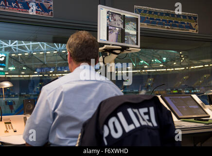 A police officer sits in a control room monitoring CCTV ...