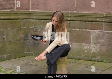 Stylish young woman with aching feet pausing in town to sit on a cement bollard as she removes her high heels to - Stock Photo