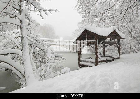 Central Park peaceful winter scene after heavy snowfall. The Bow Bridge and a wooden gazebo are covered in snow. - Stock Photo