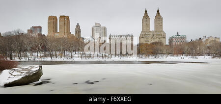 Winter morning after snowfall in Central Park and frozen lake. Manhattan Upper West buildings rise above the park, - Stock Photo