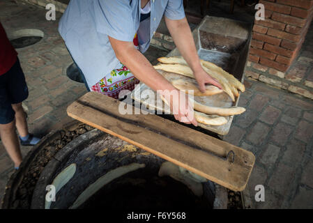 Woman shows traditional way of Shoti Bread baking in oven called tone (torne or turne) in Twins Wine Cellar, Napareuli, - Stock Photo