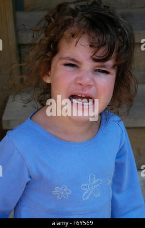 Young girl having a temper tantrum on stairs. - Stock Photo