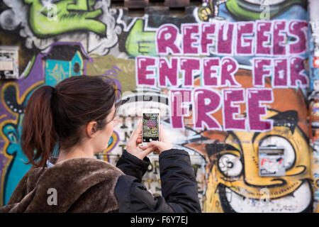 Woman taking a photo of graffiti on a wall of a Hostel in Germany - Stock Photo