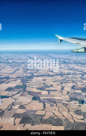 the view,  flying over the Canadian prairies, showing the patchwork for fields, crops, lakes and rivers, and wing - Stock Photo