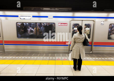 A Japanese woman waiting at the metro for a passing train - Stock Photo