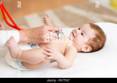 Pediatrician examines three months baby boy. Doctor using a stethoscope to listen to kid's chest checking heartbeat. - Stock Photo