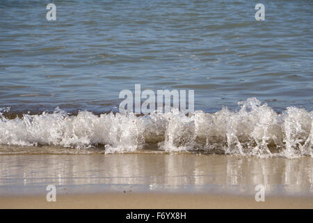 Waves gentling rolling onto a sandy beach - Stock Photo