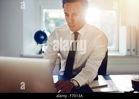 Young white business man working on computer sitting at his desk - Stock Photo