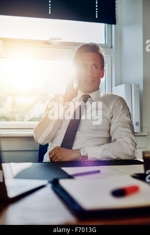 Business man speaking on the phone while sitting at his desk with documents - Stock Photo