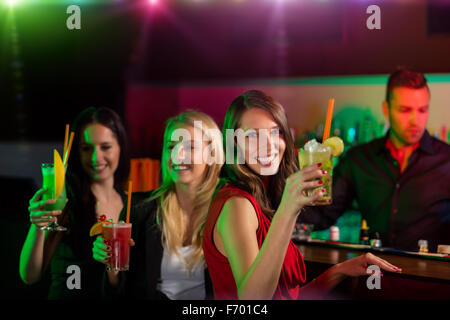 Young friends drinking cocktails together at party - Stock Photo