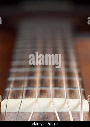 Guitar Nut and Strings on a steel string guitar - Stock Photo