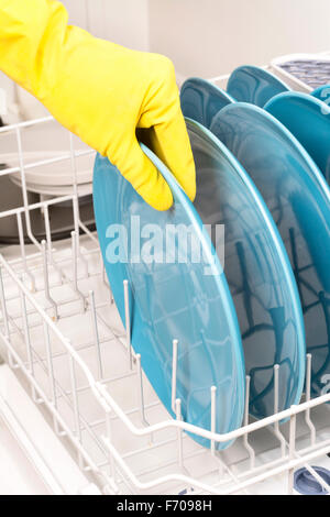 A woman removes dishes after they are finished being washed in a dishwasher