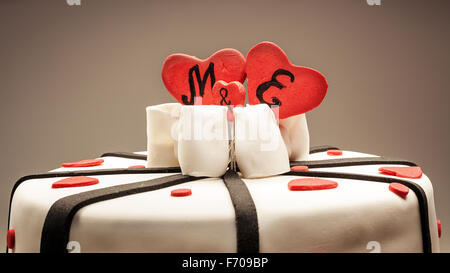 Anniversary cake decoration with red hearts and black ribbons. - Stock Photo