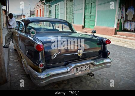 driver leaning on parked vintage car having a cigarette break in the shade on a sunny cobbled street in Trinidad - Stock Photo