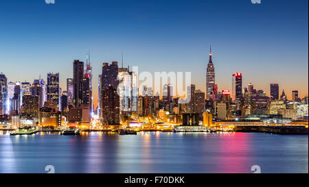 New York City skyline at dawn, as viewed from Weehawken, along the 42nd street canyon - Stock Photo