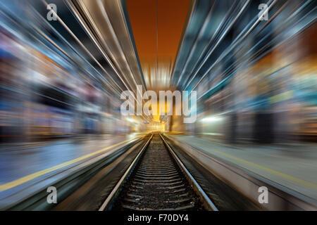 Railway station at night with motion blur effect. Cargo train platform in fog. Railroad - Stock Photo