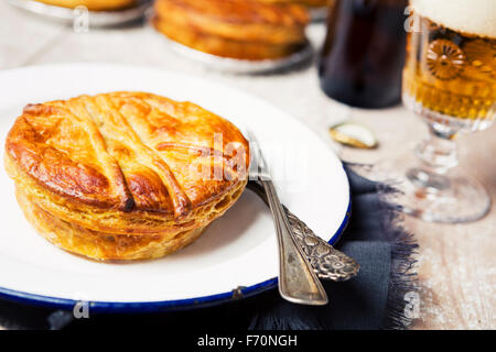 A homemade meat pie and beer on a rustic table. - Stock Photo