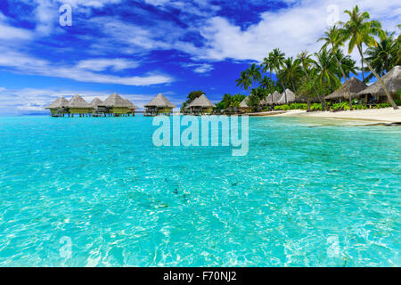 Over-water bungalows of luxury tropical resort, Bora Bora island, near Tahiti, French Polynesia, Pacific ocean - Stock Photo