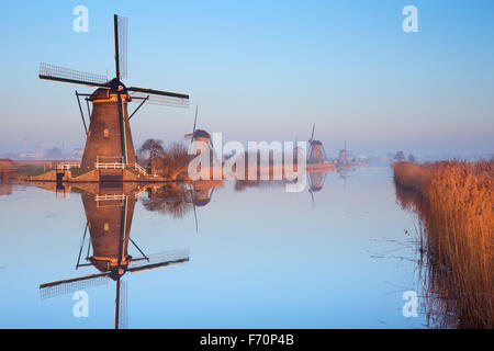Traditional Dutch windmills reflected in perfectly still water on a cold morning in winter, at the Kinderdijk in - Stock Photo