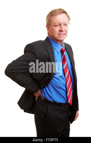Elderly businessman holding his hand to his aching back - Stock Photo