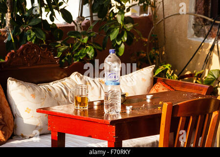 Santorini. Still life, close up of table outside Greek taverna, with water bottle and glass mug half full with beer - Stock Photo